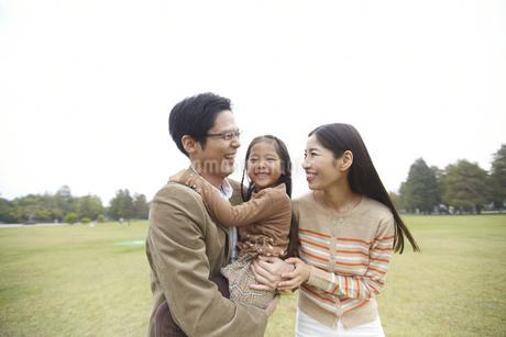 公園で娘を間に笑い合う家族の写真素材 [FYI02966936]