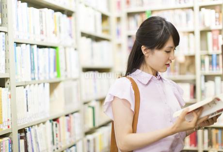図書室で立って読書をする女子学生の写真素材 [FYI02966940]