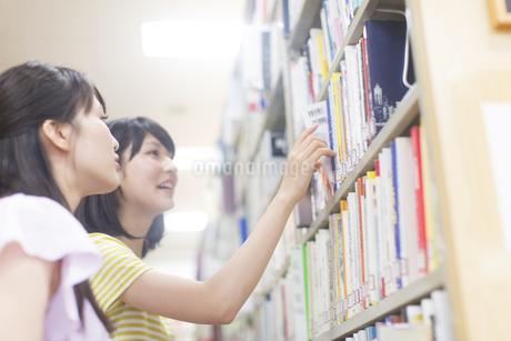 図書室で本を探す2人の女子学生の写真素材 [FYI02966943]