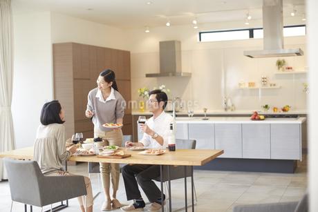 ホームパーティでワインと食事を楽しむ男女の写真素材 [FYI02966946]