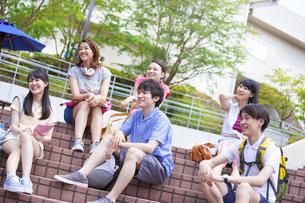 キャンパスの階段に座り笑う学生たちの写真素材 [FYI02966947]