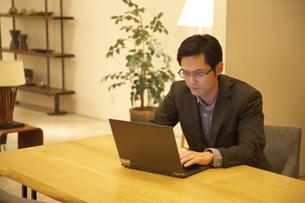 テーブルでノートパソコンを打つ男性の写真素材 [FYI02966950]
