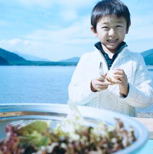 湖畔でジャガイモの皮を剥く男の子の写真素材 [FYI02966953]