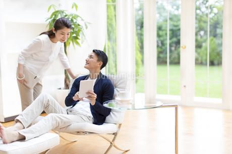 タブレットPCを見ながら話す夫婦の写真素材 [FYI02966954]