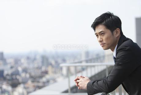 屋上で景色を眺めるビジネス男性の写真素材 [FYI02966956]