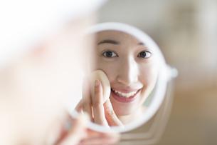 鏡の前でスキンケアをする微笑む女性の写真素材 [FYI02966957]