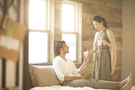 ベッドの上にいる男性にカップを手渡す女性の写真素材 [FYI02966958]