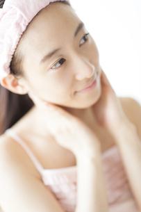 首に両手を添えて微笑む女性の写真素材 [FYI02966959]