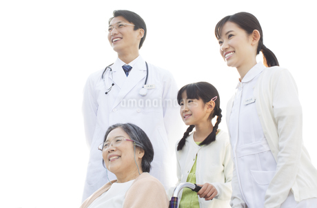 屋上で車椅子の患者に添う医師と看護師と女の子の写真素材 [FYI02966962]