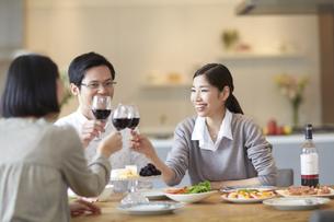 ホームパーティでワインを手に乾杯する男女三人の写真素材 [FYI02966964]