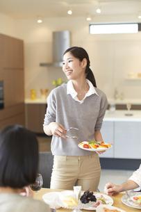 食事の皿を持って横を向いて笑う女性の写真素材 [FYI02966966]