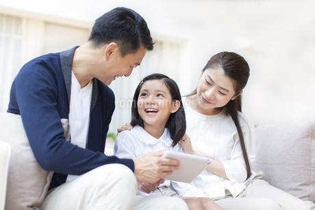 タブレットPCを見ながら笑い合う親子の写真素材 [FYI02966967]