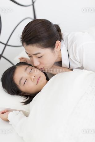 眠る娘にキスをする母親の写真素材 [FYI02966970]