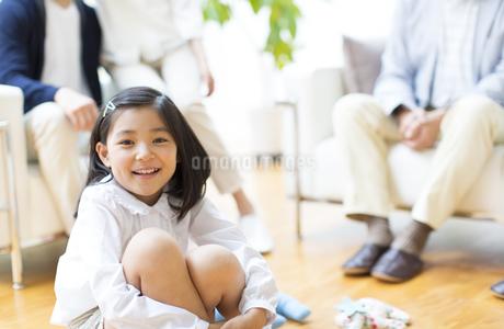 家族の前で膝を抱えて微笑む女の子の写真素材 [FYI02966977]