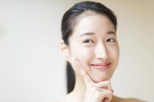 頬に指をあて微笑む女性の写真素材 [FYI02966978]