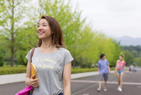 微笑みながらキャンパスを歩く女子学生の写真素材 [FYI02966985]