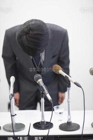 謝罪会見で頭を下げるビジネス男性の写真素材 [FYI02966986]