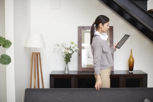 ソファーでスマートデバイスを持って歩く女性の写真素材 [FYI02966988]
