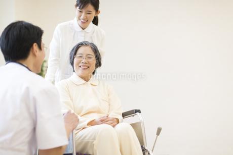 車椅子の患者に添う男性医師と女性看護師の写真素材 [FYI02966992]