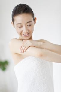腕をマッサージする微笑む女性の写真素材 [FYI02966993]