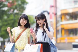 スマートフォンを持って歩く買物中の若い女性2人の写真素材 [FYI02966997]