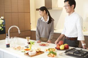 キッチンに立って微笑む夫婦の写真素材 [FYI02967001]