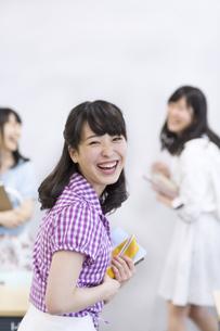 教室で笑顔で振り向く女子学生の写真素材 [FYI02967002]