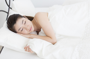 ベットで横向きに眠る女性の写真素材 [FYI02967003]