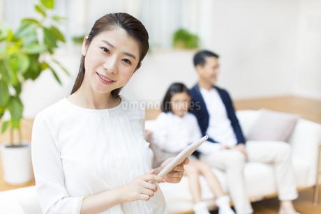 父と娘の前でタブレットPCを見る母の写真素材 [FYI02967005]