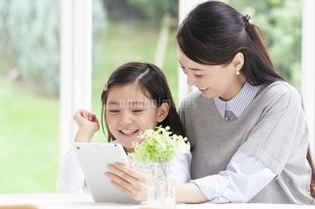母の持つタブレットPCを見て微笑む女の子の写真素材 [FYI02967009]