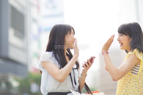 街で挨拶しあう若い女性の写真素材 [FYI02967010]