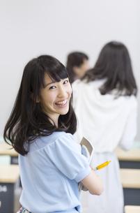 教室で笑顔で振り向く女子学生の写真素材 [FYI02967011]