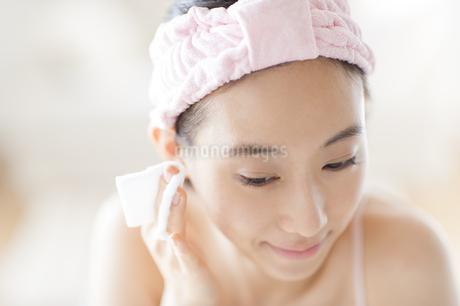 頬にコットンをあてスキンケアをする女性の写真素材 [FYI02967012]