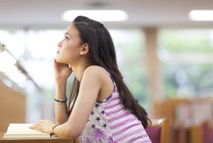図書室で読書中に顔を上げる女子学生の写真素材 [FYI02967013]