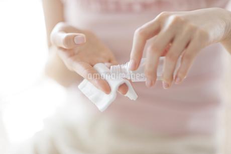 コットンに美容液を湿らす女性の手の写真素材 [FYI02967015]
