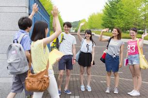 キャンパスの門で挨拶し合う学生たちの写真素材 [FYI02967017]