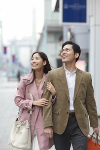 買い物中に腕を組んで歩くカップルの写真素材 [FYI02967019]