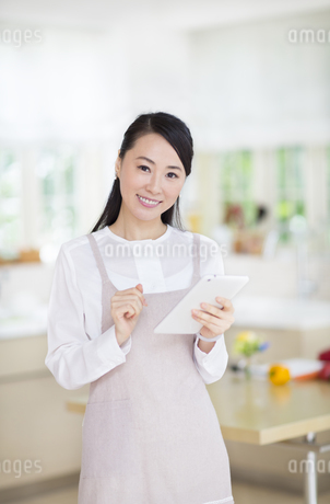 キッチンでタブレットPCを持つ奥さんの写真素材 [FYI02967021]