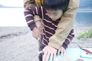 湖畔で木の工作を教わる男の子の写真素材 [FYI02967027]
