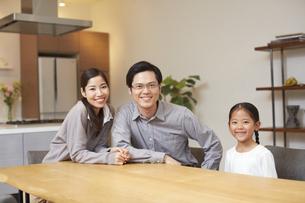 父を中心にテーブルでほほ笑む3人家族の写真素材 [FYI02967028]