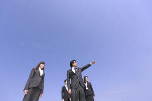 青空を背景に指をさす方向を見るビジネス男女の写真素材 [FYI02967032]