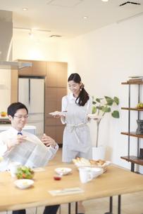 出勤前の朝食を運ぶ奥さんと新聞をたたむ夫の写真素材 [FYI02967034]