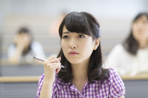 ペンを持ち考える女子学生の写真素材 [FYI02967035]