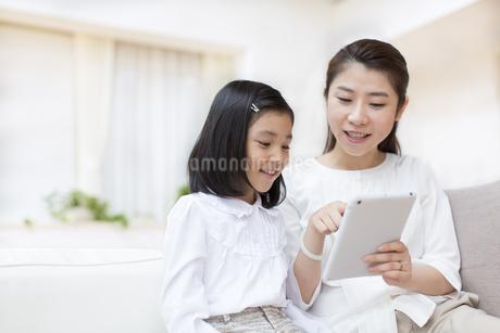 タブレットPCを見る母と娘の写真素材 [FYI02967037]