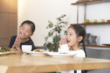 食事を前に笑顔で手を合わせる女の子の写真素材 [FYI02967039]