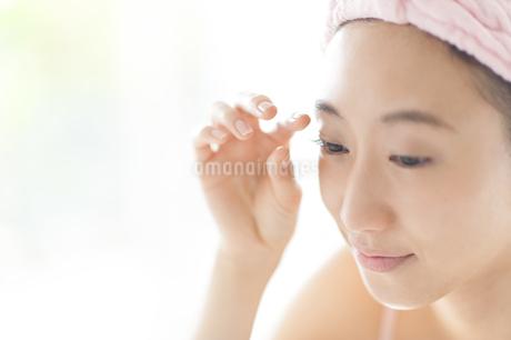 自分のまぶたをチェックする女性の写真素材 [FYI02967041]