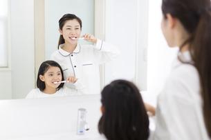 鏡に向かって歯磨きをする母と娘の写真素材 [FYI02967042]