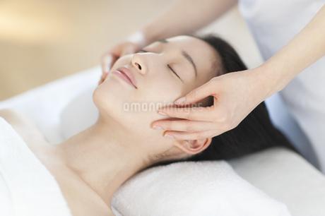 仰向けで顔をマッサージされている女性の写真素材 [FYI02967045]