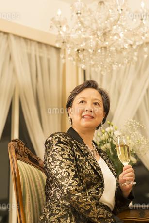 ワイングラスを手にポーズをとるシニア女性の写真素材 [FYI02967050]