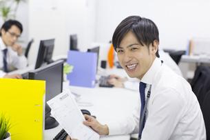 デスクで資料を手に笑うビジネス男性の写真素材 [FYI02967058]